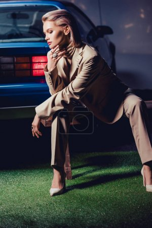 Photo for Attractive and stylish woman in suit sitting on wooden bench near retro car - Royalty Free Image