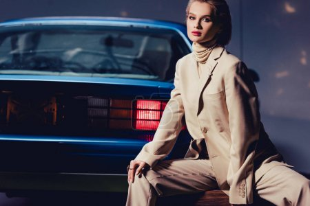 attractive and stylish woman sitting near retro car and looking at camera