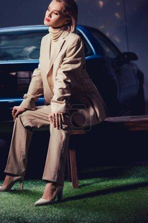 Photo pour Attrayant et élégant femme en costume assis sur banc en bois ours voiture rétro - image libre de droit