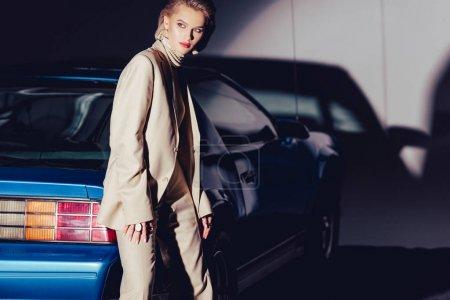 Photo pour Attrayant et élégant femme en costume debout près de voiture rétro - image libre de droit