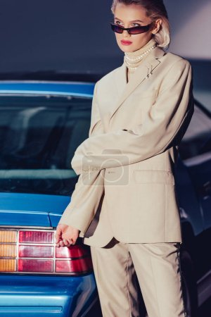 Photo for Attractive and stylish woman in suit and sunglasses standing near retro car - Royalty Free Image
