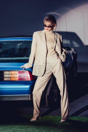 Photo pour Attrayant et élégant femme en costume et lunettes de soleil debout près de voiture rétro - image libre de droit