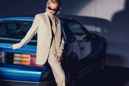 Photo pour Attractive and stylish woman in suit and sunglasses standing near retro car - image libre de droit