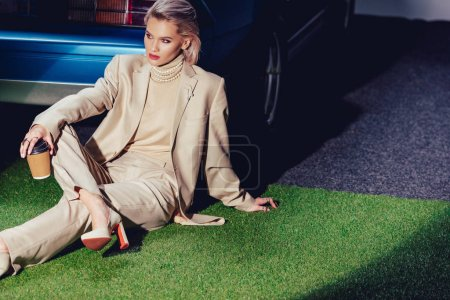 Photo pour Attractive and stylish woman in suit sitting near retro car and holding paper cup - image libre de droit