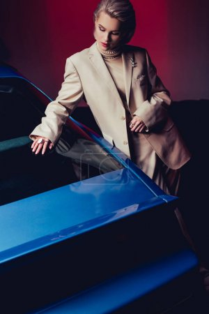 Photo for Attractive and stylish woman in suit touching retro car - Royalty Free Image