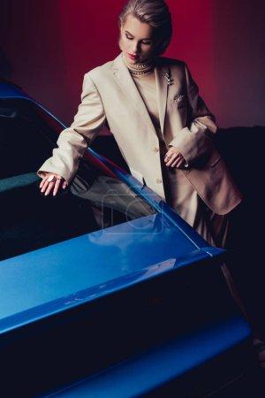 attraktive und stilvolle Frau im Anzug berührt Retro-Auto
