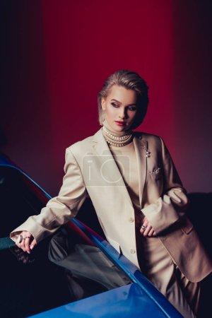 Photo pour Attrayant et élégant femme en costume toucher voiture rétro - image libre de droit