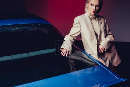attractive and stylish woman in suit touching retro car