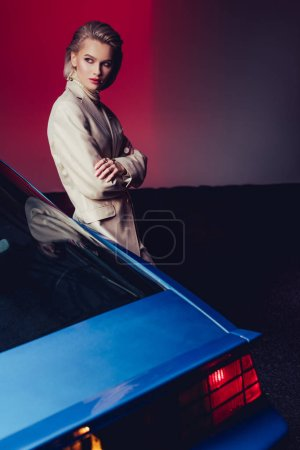 Photo pour Attractive and stylish woman with crossed arms in suit standing near retro car - image libre de droit