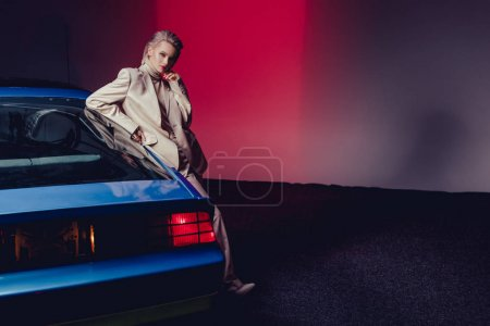 Photo for Attractive and stylish woman in suit standing near retro car - Royalty Free Image