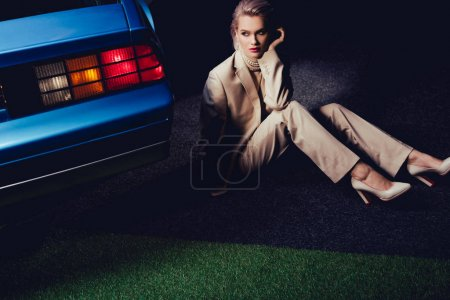 Photo for Attractive and stylish woman in suit sitting near retro car - Royalty Free Image