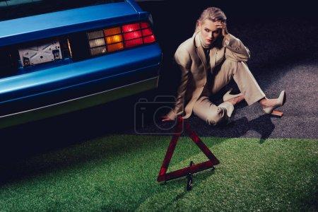 Photo pour Attractive and stylish woman in suit sitting near retro car - image libre de droit