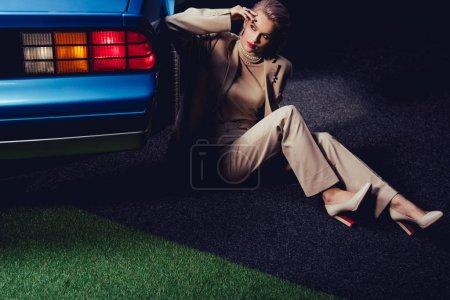 Photo pour Attrayant et élégant femme en costume assis près de voiture rétro - image libre de droit