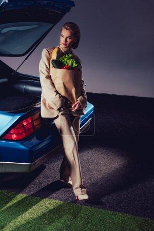 Photo pour Séduisante et élégante femme en complet debout près d'une voiture rétro et tenant un sac en papier avec de la nourriture - image libre de droit