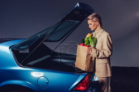 Photo for Side view of attractive and stylish woman in suit standing near retro car and holding paper bag with food - Royalty Free Image