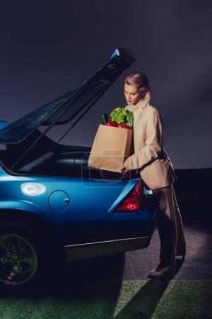 Photo pour Attrayant et élégant femme en costume emballage sac en papier avec de la nourriture dans le coffre - image libre de droit