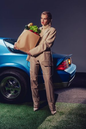 Photo pour Attractive and stylish woman in suit standing near retro car and holding paper bag with food - image libre de droit