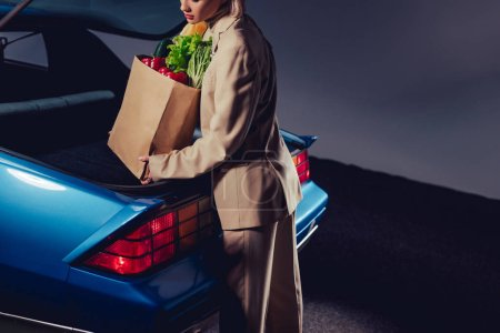 Photo pour Cropped view of stylish woman in suit packing paper bag with food in trunk - image libre de droit