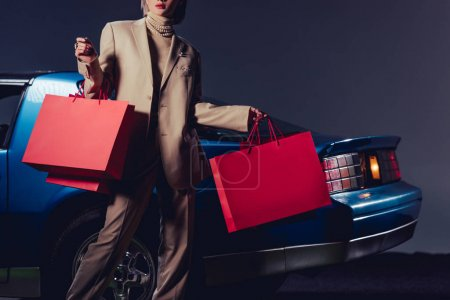 Photo pour Cropped view of woman in suit standing near retro car and holding shopping bags - image libre de droit