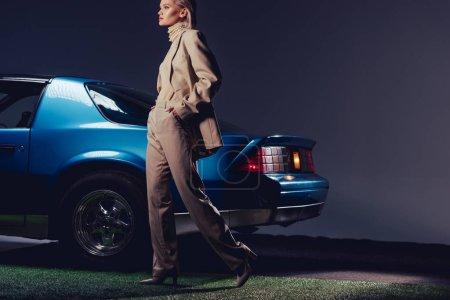 Photo pour Attractive and stylish woman in suit walking near retro car - image libre de droit