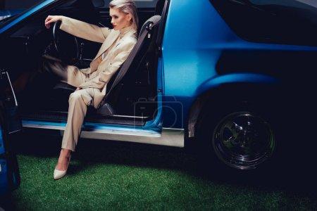 Photo pour Attrayant et élégant femme en costume assis dans la voiture rétro - image libre de droit
