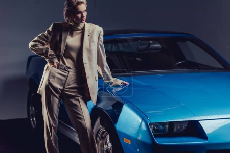 Photo for Attractive and stylish woman in suit with hands on hip standing near retro car - Royalty Free Image