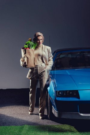 attractive and stylish woman in suit standing near retro car and holding paper bag with food