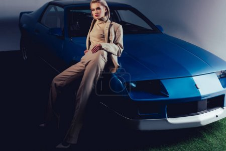 Photo for Attractive and stylish woman in suit sitting on retro car - Royalty Free Image