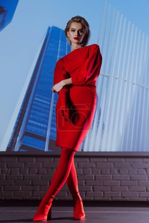 Photo for Attractive and stylish woman in red dress on city background - Royalty Free Image