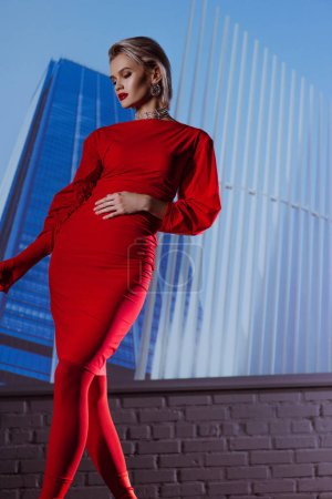 Photo pour Low angle view of attractive and stylish woman in red dress on city background - image libre de droit