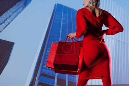 Photo for Cropped view of stylish woman in red dress holding shopping bags on city background - Royalty Free Image