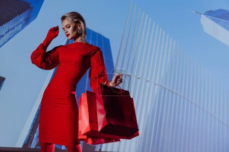Photo for Low angle view of attractive and stylish woman in red dress holding shopping bags on city background - Royalty Free Image