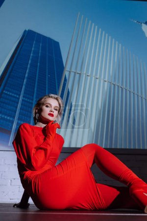 Photo for Attractive and stylish woman in red dress sitting on city background - Royalty Free Image