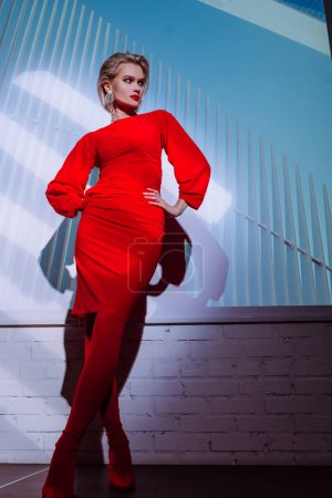 Photo for Low angle view of attractive and stylish woman in red dress with hands on hips on city background - Royalty Free Image