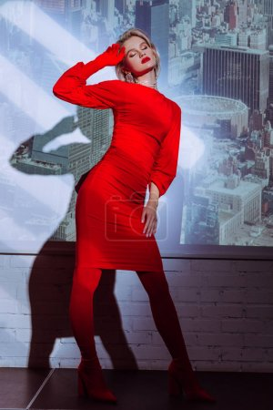 Photo for Attractive and stylish woman with closed eyes in red dress on city background - Royalty Free Image