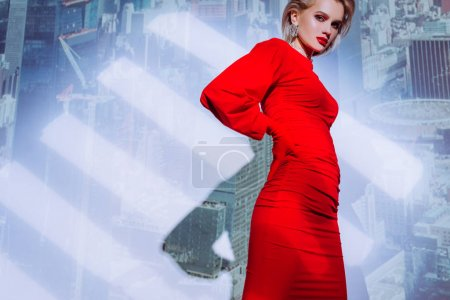 Photo for Low angle view of attractive and stylish woman in red dress on city background - Royalty Free Image