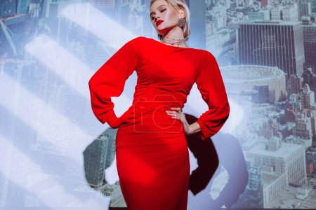 Photo pour Low angle view of attractive and stylish woman with hands on hips in red dress on city background - image libre de droit