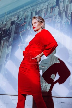 Photo for Low angle view of attractive and stylish woman with hand on hip in red dress on city background - Royalty Free Image