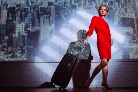 Photo for Low angle view of attractive and stylish woman in red dress holding travel bag on city background - Royalty Free Image