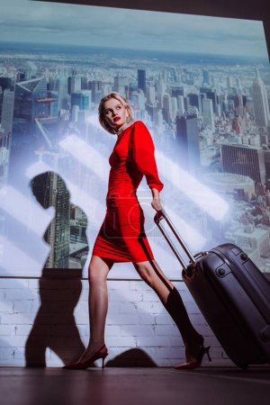 Photo pour Vue à faible angle d'une femme séduisante et élégante en robe rouge marchant avec un sac de voyage sur fond de ville - image libre de droit