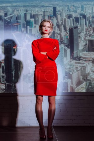 Photo for Attractive and stylish woman in red dress with crossed arms on city background - Royalty Free Image
