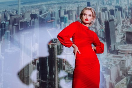 Photo for Attractive and stylish woman in red dress with hands on hips on city background - Royalty Free Image