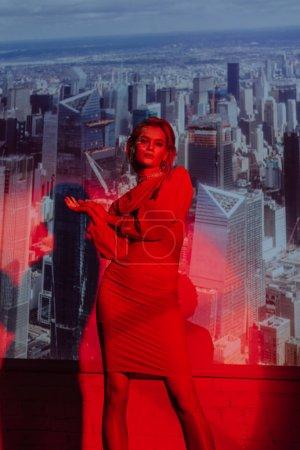 Photo pour Femme attrayante et élégante en robe rouge sur fond de ville - image libre de droit
