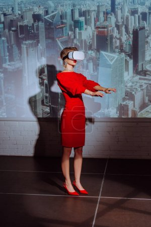 Photo for Stylish woman with outstretched hands in red dress and virtual reality headset on city background - Royalty Free Image