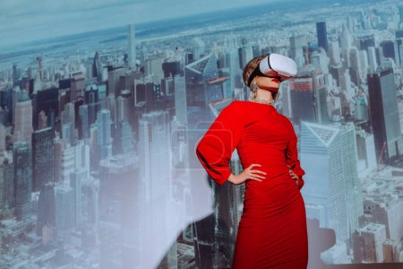 Photo for Low angle view of stylish woman with hands on hips in red dress and virtual reality headset on city background - Royalty Free Image