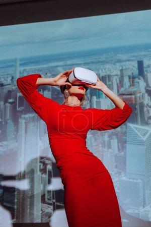 """Photo pour Vue à faible angle d'une femme de style en robe rouge et casque d """"écoute en réalité virtuelle sur le fond de la ville - image libre de droit"""