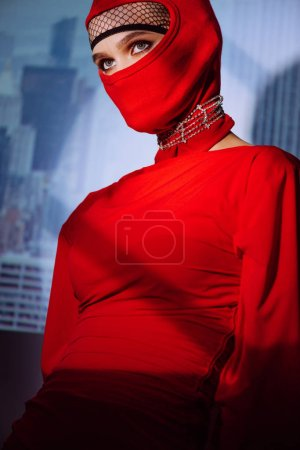 Photo for Stylish woman in red dress and balaclava on city background - Royalty Free Image