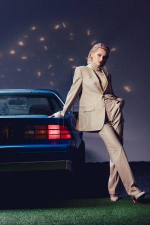 Photo pour Attractive and stylish woman in suit standing near retro car - image libre de droit