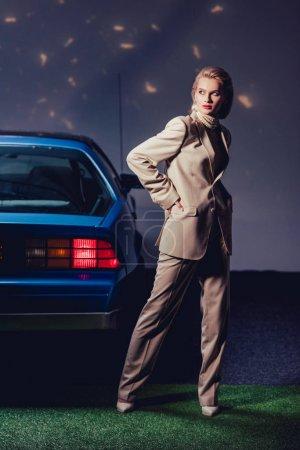 Photo pour Attrayant et élégant femme en costume debout rétro près de la voiture - image libre de droit