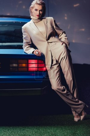 Photo for Attractive and stylish woman in suit lying on retro car - Royalty Free Image
